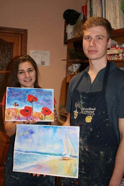 девочка и мальчик держат нарисованные картины